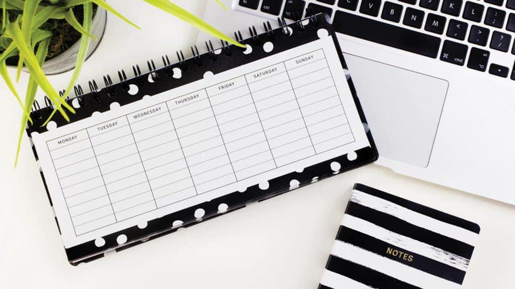 Calendario, libreta y ordenador sobre una mesa